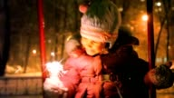 Little girl teetering and holding sparkler in hand, night outdoor video