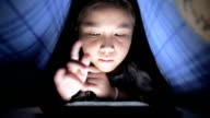 Little girl using tablet under the blanket video
