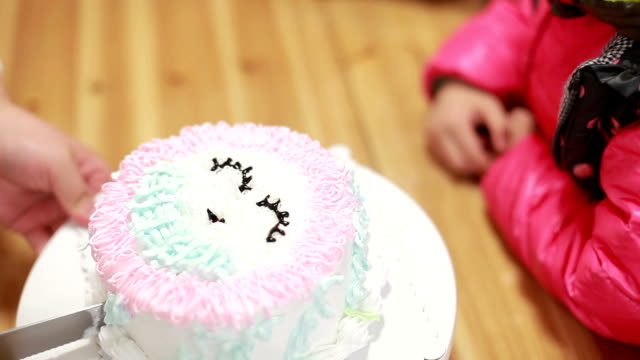little girl wait the birthday cake to be cut into pieces. video
