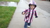 Little girl walking along sidewalk in rain video