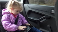 Little girl warm clothing, playing on your tablet PC in car video
