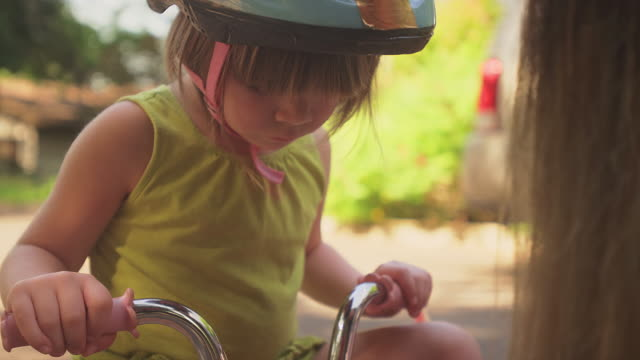 A little girl watches as her mom puts tape on her bike video