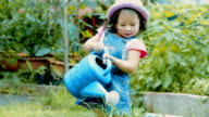 Little girl watering plant in garden \\ Concept : taking care of nature video
