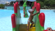 Little girl with bandana afraid to go down the slide in aquapark video