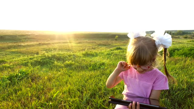 Little girl with enthusiasm plays on the tablet PC. Girl child with glasses stands on a green meadow. video