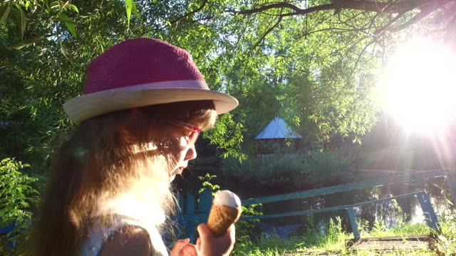 Little girl with long hair eats ice-cream in the park. video