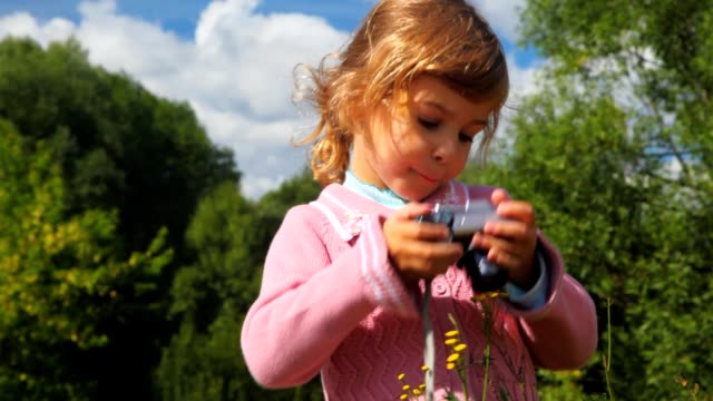 Little girl with photo camera in park video