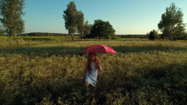 Little girl with red umbrella waves hand and walks on the meadow video