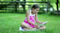 Little girl with tablet pc sits on the grass in garden video