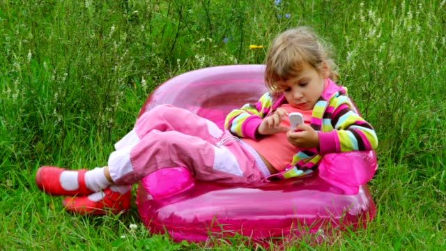 Little girl with telephone lying on inflatable armchair video