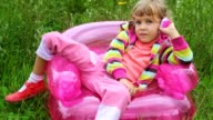 Little girl with telephone sitting on inflatable armchair video