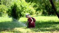 Little girl with watering Sprinkle hot day. video