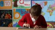 Little girl writes E=mc2 on blackboard video