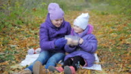 little girls are drinking cocoa in the fresh air. autumn Park. slow-motion video