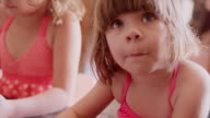 Little girls at a kitchen counter helping their mom bake video
