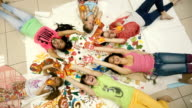 Little girls lie on the floor in the picture and waving their hands. video