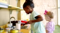 Little girls participate in creative play in a toy kitchen video