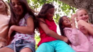 Little girls sitting on fence under a treehouse in summer video