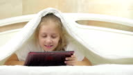 Little girls using tablet on the bed. video