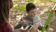 Little painter and his mother paint autumn picture in park video