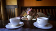 A little pretty girl is sitting on the sofa at a cafe and hugging her stuffed rabbit video