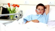 Little sick boy sitting in bed with thermometer video
