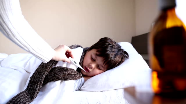 little sick boy with digital thermometer video