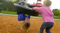 Little sister pushes tire swing while big sister hangs from below video