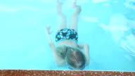 Little smiling girl with goggles in blue water swimming pool video