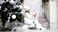 Little snow elf sitting under the tree with a doll on the steps near the door video