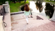 Lively girl happily run downstairs, picturesque staircase to the pond, slowmo video