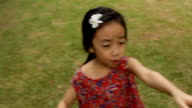 Llittle girl running with a big smile in the garden video