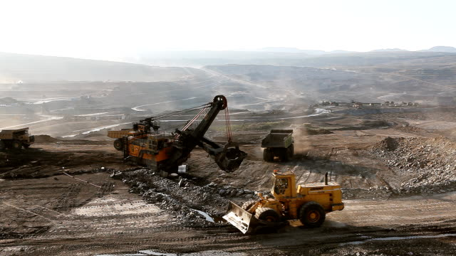 Loading of iron ore on very big dump-body truck. video