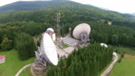 Location with big satellite antennas array and communications tower , electronic equipment for signal broadcasting over mountain area  , aerial view video
