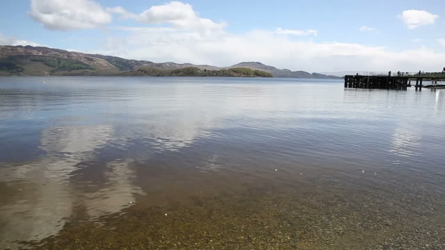 Loch Lomond Scotland UK in summer with clear water mountains and jetty video