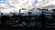 Locked bicycles on pier of Helsinki South Harbor, light up clouds on sunset sky video