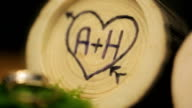 Logs with initials of lovers in heart like wedding decor video