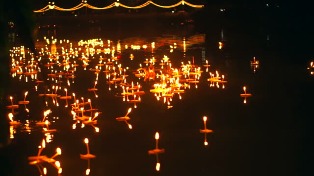Loi Krathong Festival in Chiangmai, Thailand. Hand releasing floating decorated baskets and candles to pay respect to river goddess. Thai traditional culture on full moon night video