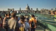 London, people crossing Thames river on Millennium bridge video
