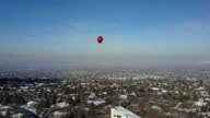 Lone red balloon floating high over city video