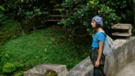 Lone woman with black hair, veiled headscarf, dressed in a blue T-shirt and kerchief tied around the legs, standing on the stone bridge in the middle of the green jungle and looking thoughtfully video