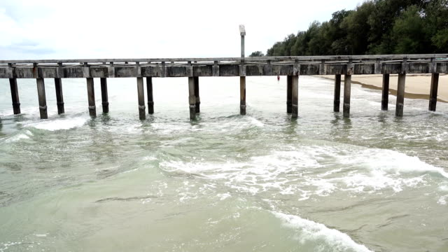 Loneliness Pier Port into the Ocean, Sandy Beach with Wave to cover and fall down, bubble on surface and spiral clear water video