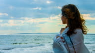 Lonely beautiful woman covered with scarf standing near sea, looking video