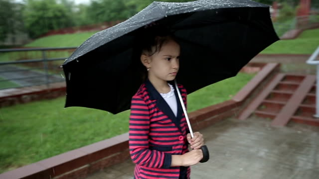 Lonely child girl in the rain with umbrella. Slow motion. video
