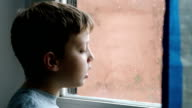lonely child looking out of the window in a rainy day video