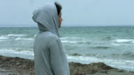 Lonely depressed woman looking at stormy sea, thinking of suicide. video