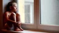 Lonely little boy waits for his parents to come home sitting on the windowsill video