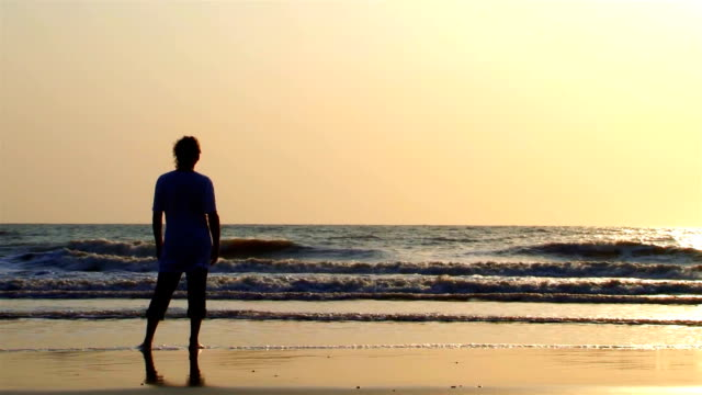 Lonely man near the ocean, slow waves video