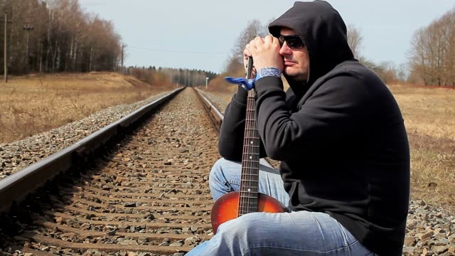 Lonely Man with guitar on the railway video