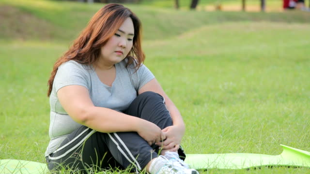Lonely overweight asian woman in the park video